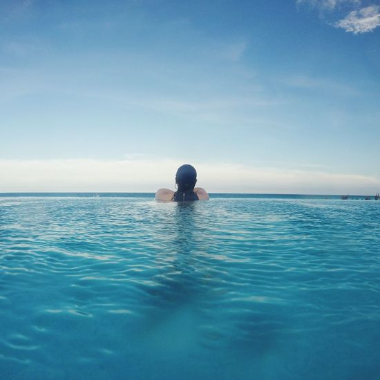 Rear view of woman relaxing in infinity pool against sky