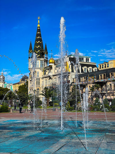 Fountain in front of building against blue sky