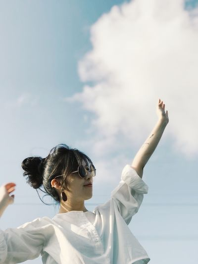 Young woman with arms raised looking away against sky