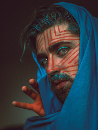 Close-up portrait of man with face paint wearing headscarf against black background