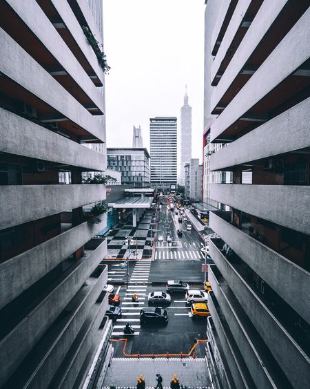 Traffic on road in city seen through buildings