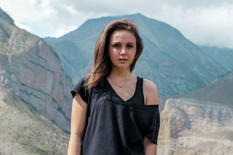 Portrait of beautiful young woman standing against mountain range