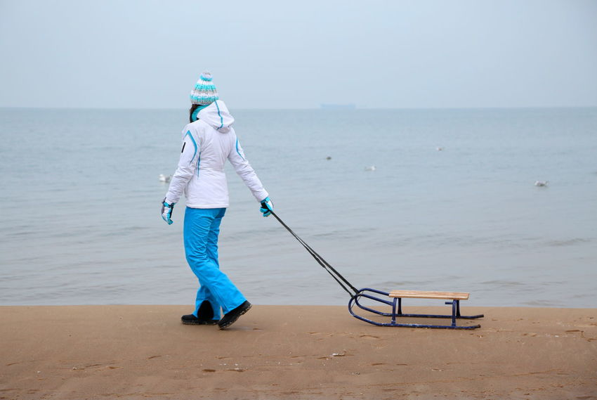 Adult Baltic Sea Beach Day Full Length Horizon Over Water Lonely Nature Nature No Snow  One Person Outdoors People Sand Sea Sky Sled Sledge Sleigh Standing Walking Around Water Winter