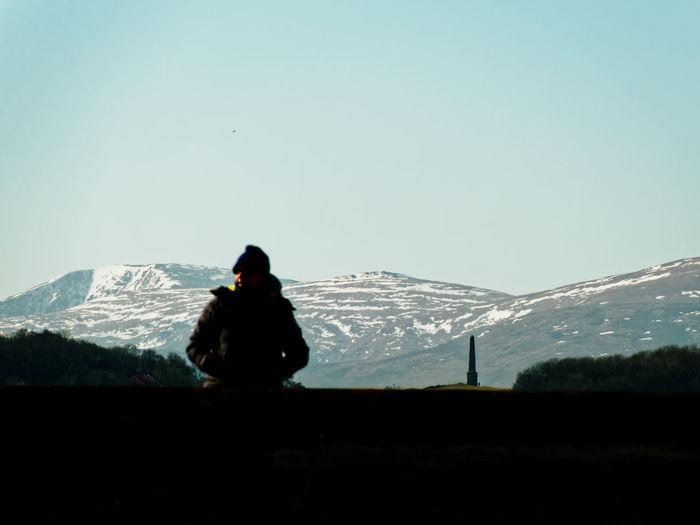 Man on mountain against clear sky