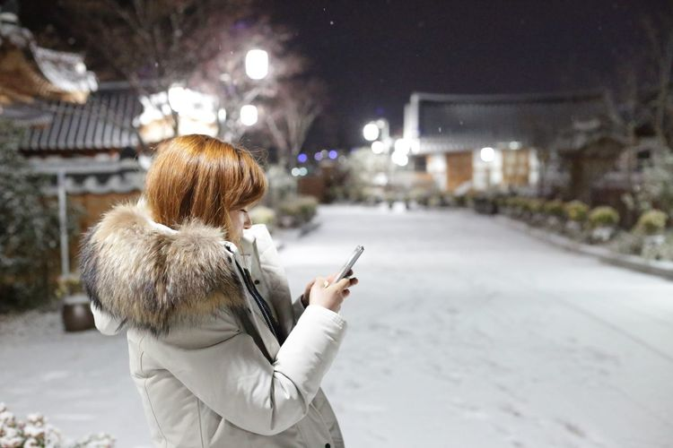 Woman using phone while standing in illuminated city during winter