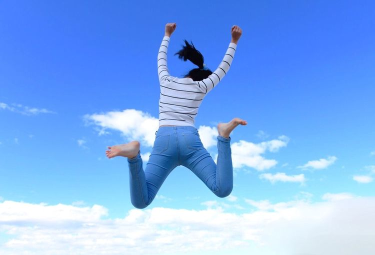 Rear View Of Woman Jumping In Mid-Air Against Sky