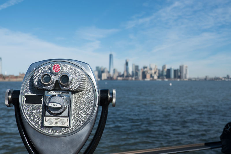 Tower viewer binoculars that look like a face on Liberty Island with New York Harbor and the Manhattan skyline in the distance. Blue skies, bright beautiful day for New York sightseeing. Ellis Island  Hudson River Hudson River Ny Liberty Island Manhattan Manhattan New York Manhattan Skyline Manhattan, New York City New York City New York City Photos New York Harbor New York Skyline  New York ❤ New York, New York Sightseeing Statue Of Liberty Statue Of Liberty New York Tower Viewer