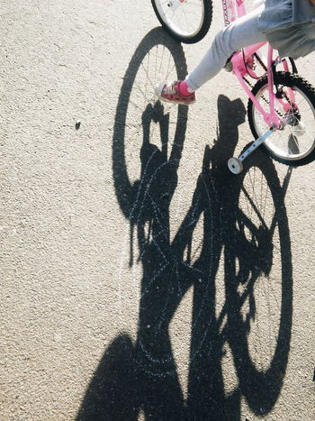 girl riding a pink bike, casting a long shadow Cycling Girls Bike Kids Bike Lifestyles Long Shadows Outdoors Pink Pink Bike Cycle Road Shadow Street Sunny Transportation
