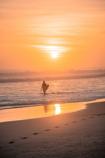 The beach of Mejia. Mejia Beach Sand Outdoors Water Nature South America Latin America Explore Surf Sport Sunset Sea Land Real People Horizon Over Water Silhouette Leisure Activity Sun Scenics - Nature Beauty In Nature Footsteps Surfboard Orange Color Lifestyles One Person