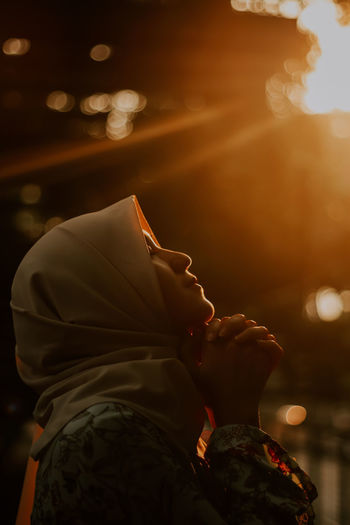 Side View Of Young Woman Praying While Standing Outdoors During Sunset