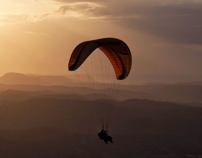 Extreme Sports Adventure Mid-air Leisure Activity Parachute Sunset Silhouette Paragliding Real People Flying Lifestyles Nature Two People Sky Sport Outdoors Mountain Scenics Day People