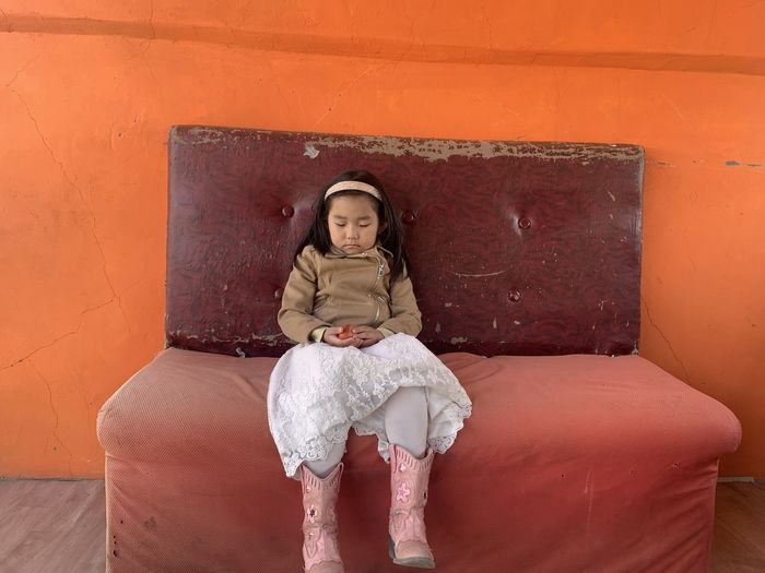 Girl with eyes closed sitting on sofa against wall