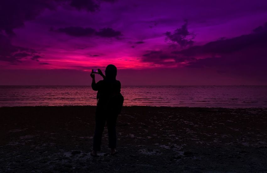 Taking photos using a smartphone Sunset Silhouette Beach Sky Beauty In Nature Scenics Nature One Person Full Length Lifestyles