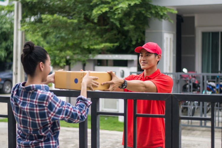 Man delivering package to female customer at gate