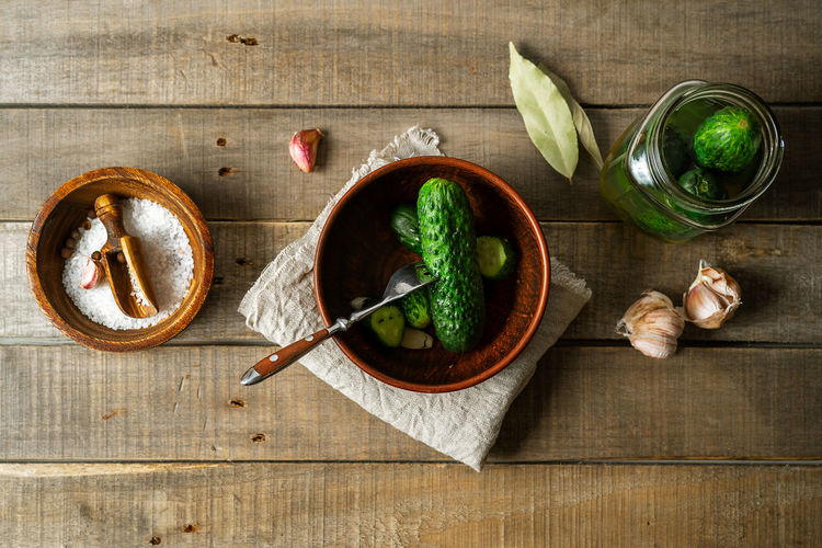 Salted cucumbers, condiments on wooden rustic background, top view