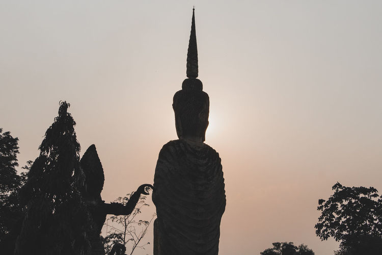 Silhouette of statue against sky during sunset