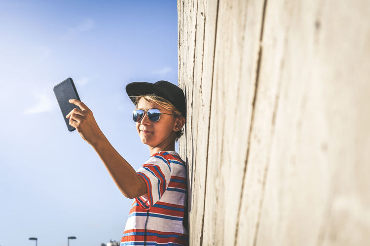 Side view of boy taking selfie from phone while standing by wall