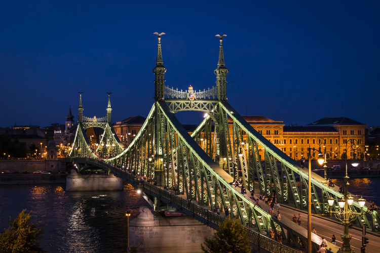 View of suspension bridge over river in city at night
