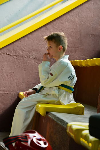 Thoughtful Boy In Sports Clothing Sitting On Steps