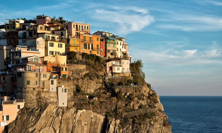 Houses on cliff by sea against sky