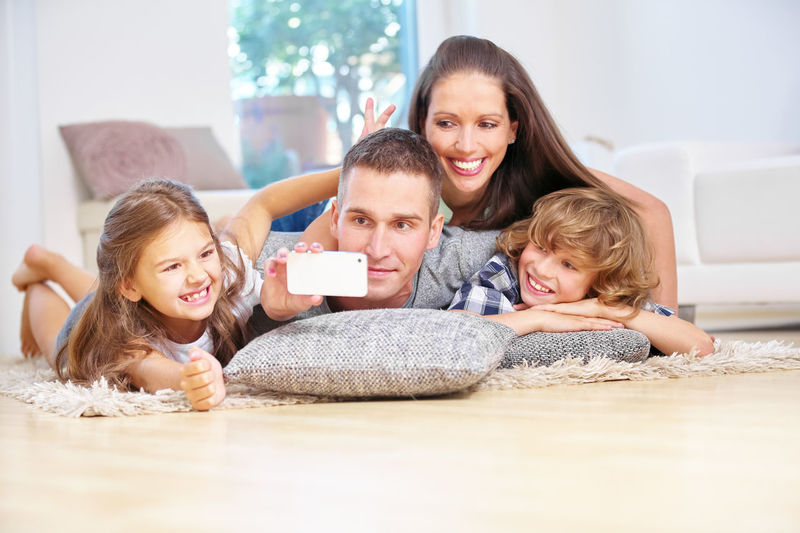 Happy Man Taking Seflie Of Family Lying On Rug At Home