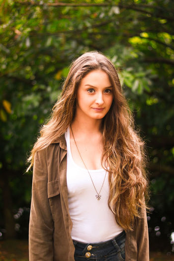 Beautiful Woman Casual Clothing Day Focus On Foreground Front View Leisure Activity Lifestyles Long Hair Looking At Camera Nature One Person Outdoors Portrait Real People Smiling Standing Tree Waist Up Young Adult Young Women