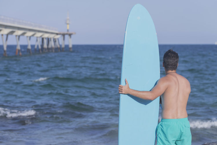 Rear view of shirtless man standing with surfboard at beach