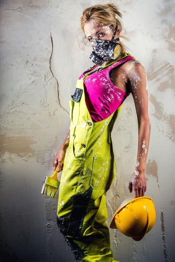Portrait Of Female Worker In Coverall Wearing Respirator While Standing Against Wall