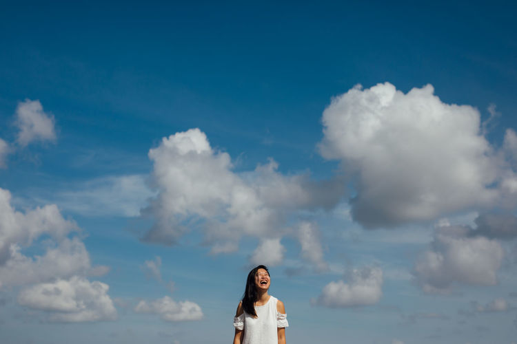 Low angle view of happy woman standing against sky