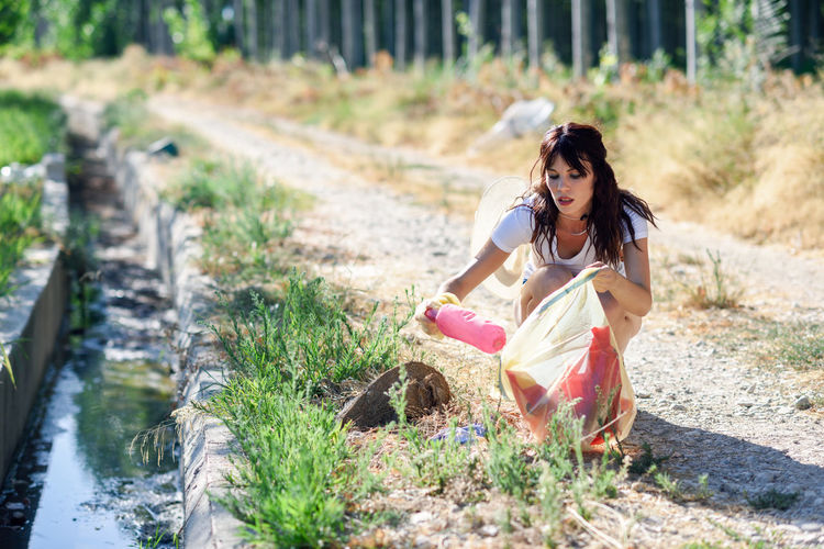 Young woman picking up garbage from dirt road