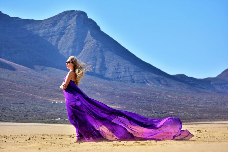 Woman holding purple fabric walking on sand against sky