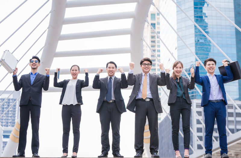Portrait of smiling businesspeople gesturing against buildings in city