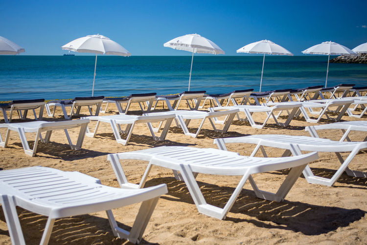Deck chairs on beach by sea against sky