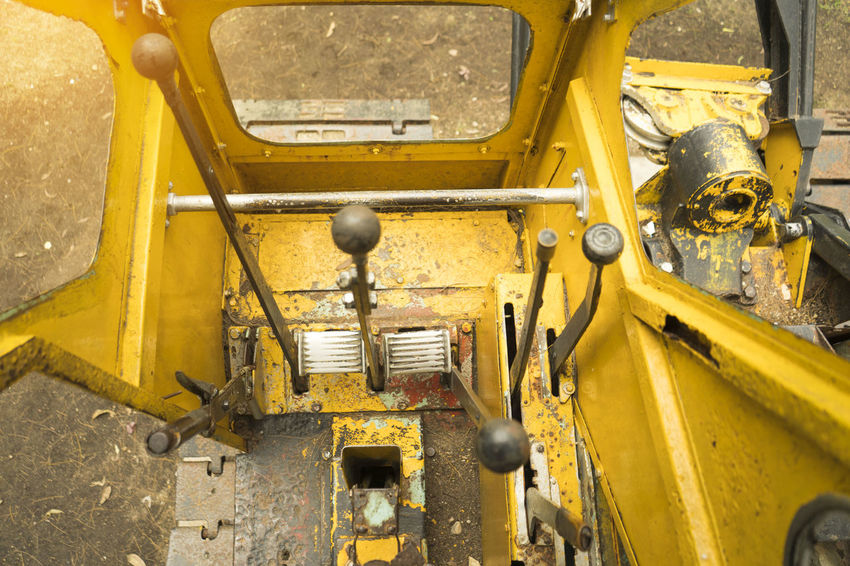 The old yellow digger was parked in a park ,Inside the loader gear Bulldozer Industrial Machinery Backhoe Bucket Damaged Day Equipment Excavation Gear Headlight High Angle View Land Vehicle Loader Backhoe Metal Mode Of Transportation Motor Vehicle No People Obsolete Old Retro Styled Stationary Transportation Travel Yellow