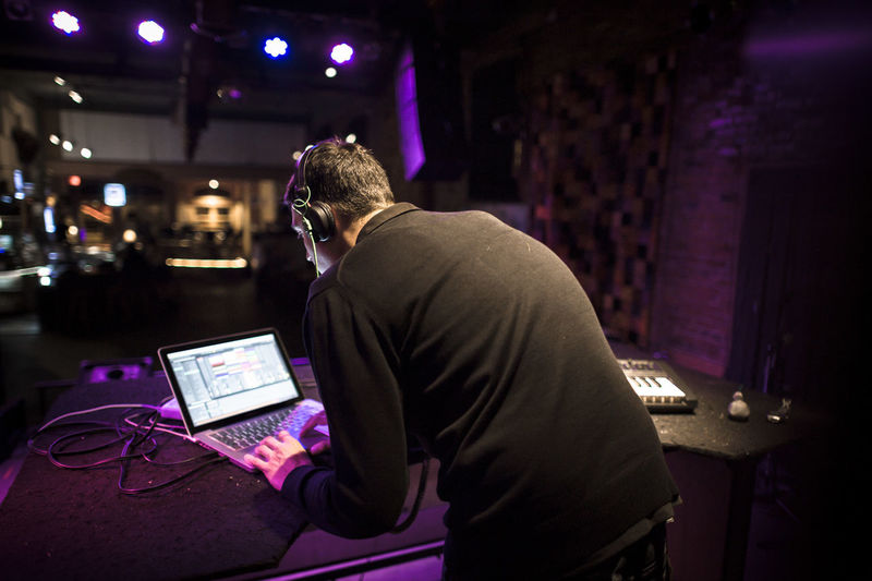 Rear view of man using laptop while standing in nightclub