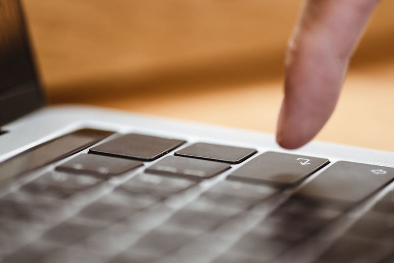 Cropped image of hand using computer keyboard