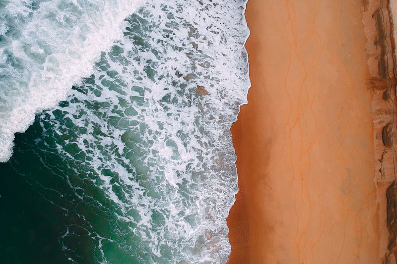 aerial view of sea waves water texture background Water Sea Wave Motion Sport Aquatic Sport Beauty In Nature Surfing Scenics - Nature Beach Nature Land High Angle View Outdoors Day Power Power In Nature Remote