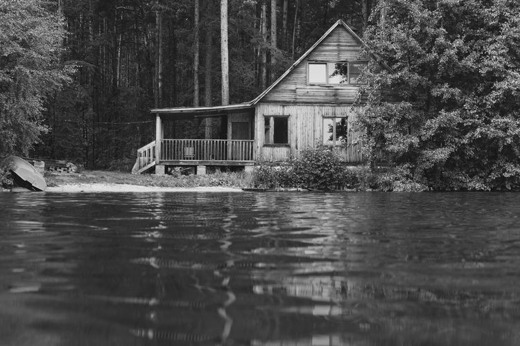 View of cottage by lake in forest