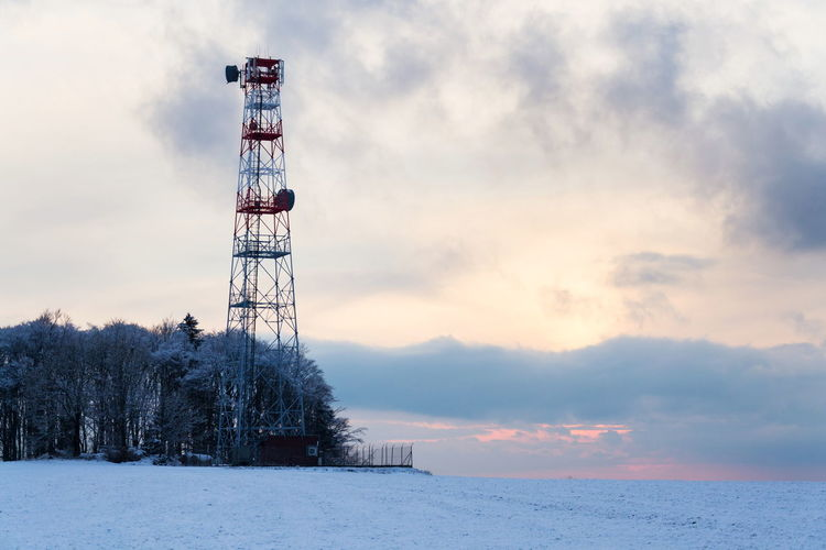 Communications tower on snow covered land against sky during sunset