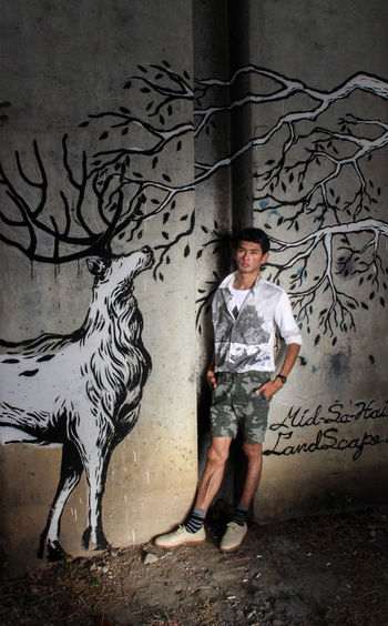 Portrait of young man standing against graffiti wall