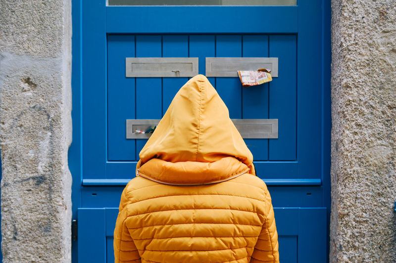 Rear view of person wearing raincoat standing in front of closed door