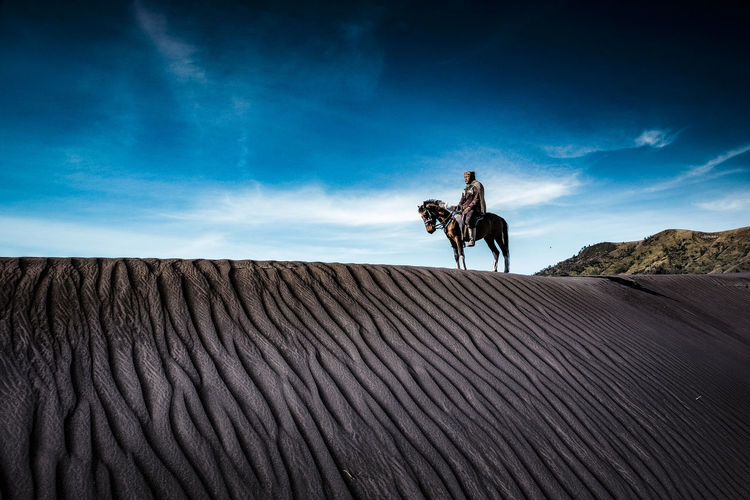Mid Adult Man Riding Horse On Sand At Desert Against Sky