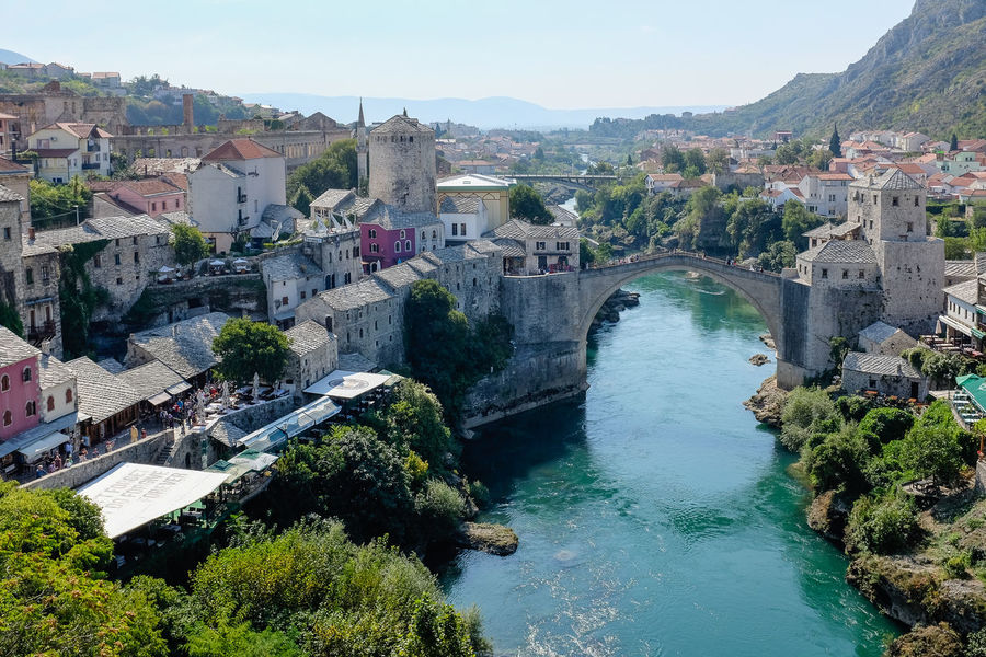 View overlooking Mostar Bridge, Bosnia Mostar Mostar Bridge Architecture Beauty In Nature Building Exterior Built Structure Clear Sky Day High Angle View Nature Outdoors River River Tara Sky Stari Most Tourism Travel Destinations Tree Water