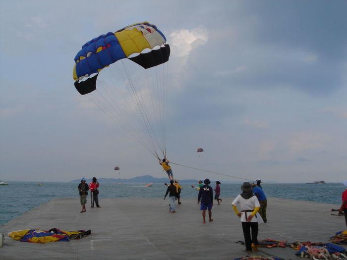 People enjoying parasailing at beach