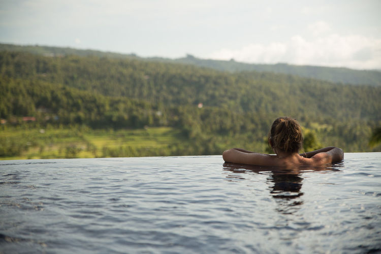 Rear view of young woman in infinity pool against clear sky