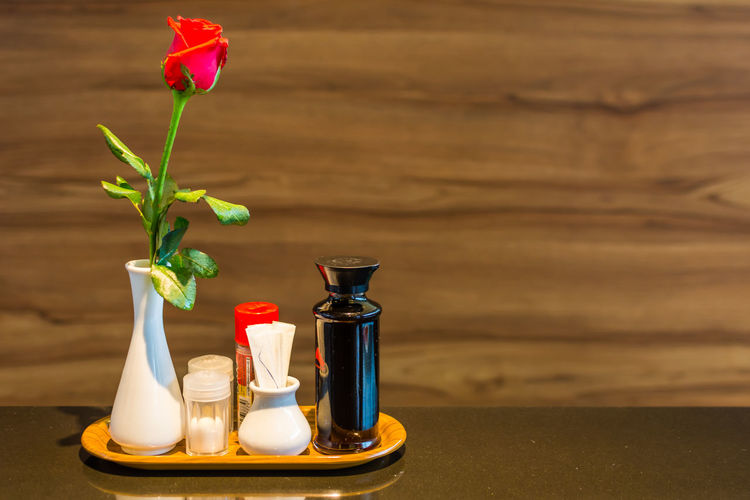 Rose in vase and shakers on tray at restaurant table