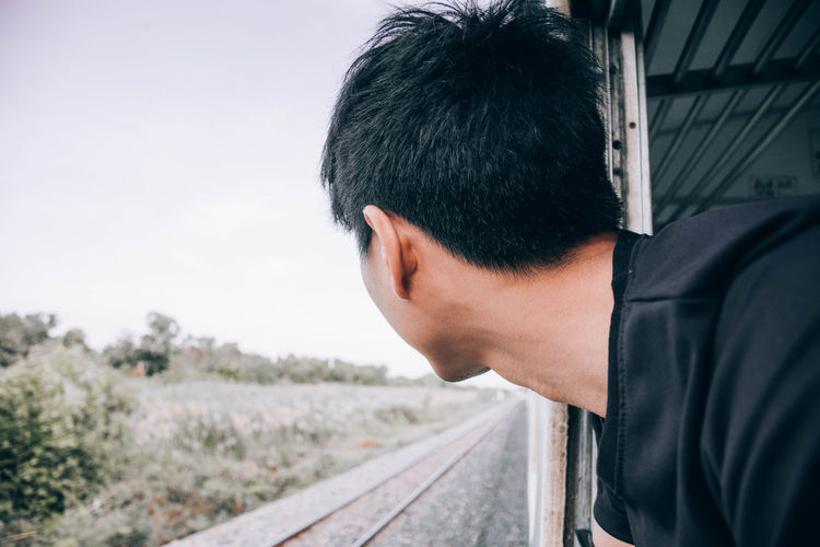 Side view of young man looking through train window