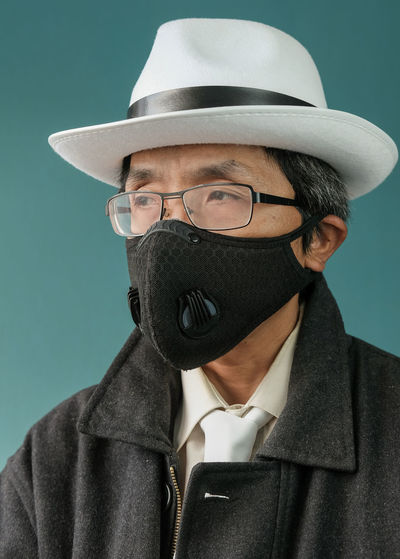Man wearing mask and hat looking away against colored background