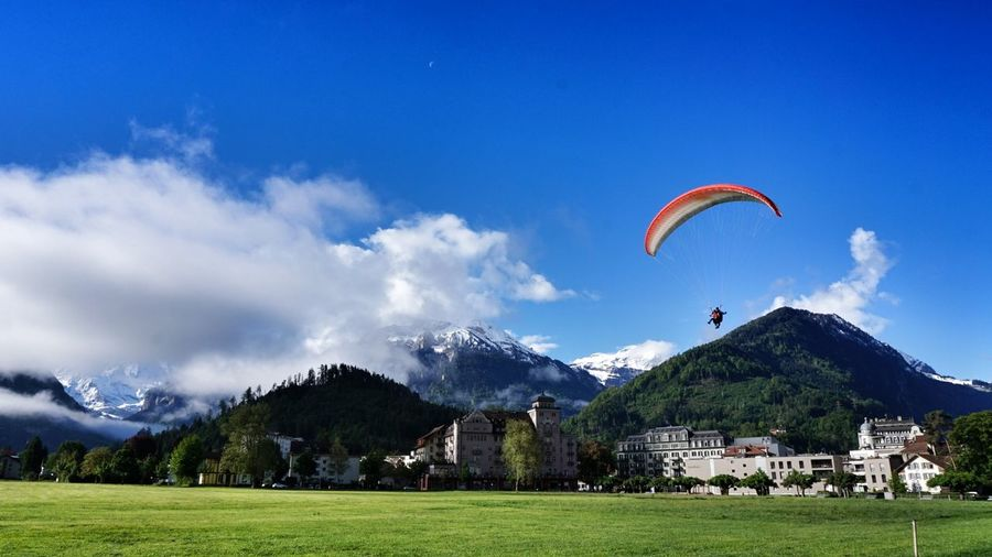 Sky Flying Paragliding Activity Grass Nature Outdoors Interlaken Clouds And Sky Travel Destinations Switzerland Bernese Oberland Eye4photography  Alps Switzerland Mountain Green Color Means Of Transportation Cloud Formations