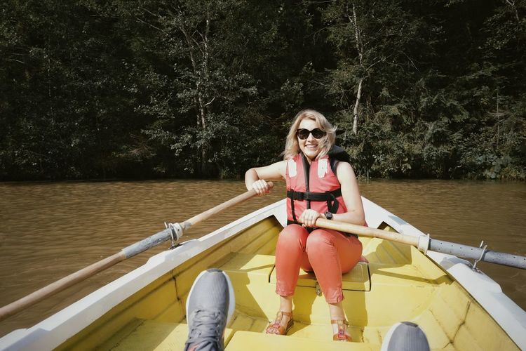 Portrait of smiling woman boating on lake